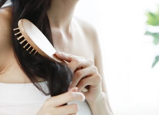 Youuse a boar bristle brush or wet brushng Woman Brushing Hair By Window